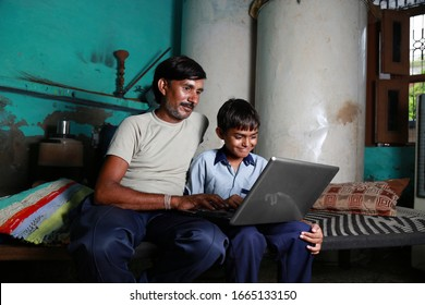 New Delhi, India - August 06, 2014: Father & son using laptop at home.