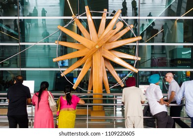 NEW DELHI, INDIA - CIRCA APRIL 2017: People stand in front of the world's largest charkha (spinning wheel) at Indira Gandhi International Airport.