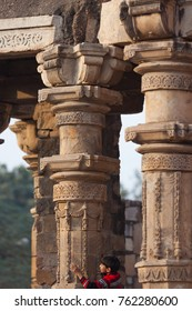 New Delhi / India - December 15 2016: Small boy is hugging ancient column of Qutub Minar Mosque