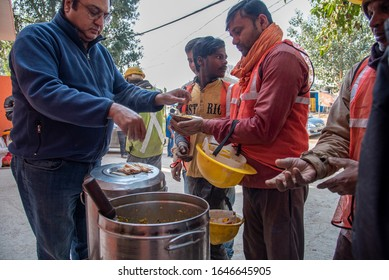 New Delhi, India - February 02, 2020: Construction workers taking 1bowl of food given by an NGO. 20% of Indian population is chronically hungry & below poverty line and do not get 3 time meal a day.