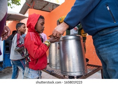 New Delhi, India - February 20, 2020: A kid in a queue taking food at a free food distribution centre set up by an NGO.