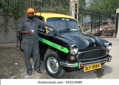 NEW DELHI, INDIA - FEBRUARY 21, 2006: A taxi driver , taking a tea near of his car in a transport station of the city of New Delhi