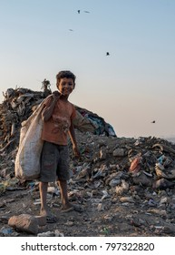 New Delhi, India - January 19, 2018: A young poor Indian boy collection waste plastic bottles in his sack to earn his livelihood.
