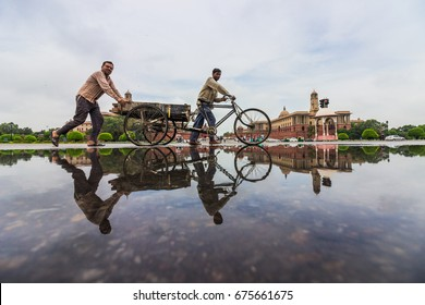 NEW DELHI, INDIA. JULY 2,2017. : Reflection of people moving a tricycle at RajPath, New Delhi, India after monsoonal rains.