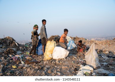 New Delhi, India - July 25, 2018: A group of poor children collecting garbage waste from a landfill site in the outskirts of Delhi. Hundreds of children work at these sites to earn their livelihood.