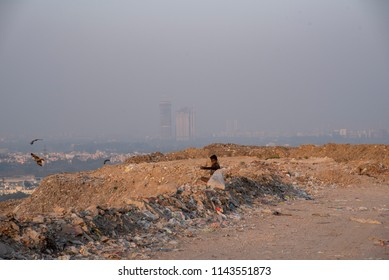 New Delhi, India - July 25, 2018: A poor boy collecting garbage waste from a landfill site in the outskirts of Delhi. Hundreds of children work at these sites to earn their livelihood.