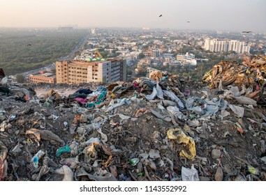 New Delhi, India - July 25, 2018: A photo taken from the top of a waste landfill site showing the buildings of New Delhi with forest cover on other side of the building.