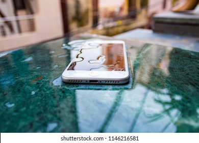 New Delhi, Delhi / India - July 25, 2018: Water drop on front side and lock screen of silver product of Apple iPhone 7 with Splash, Water, and Dust Resistant feature.
