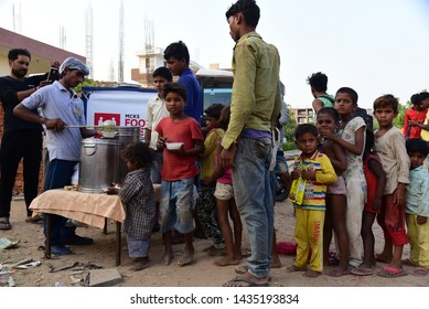 New Delhi, India - June 23, 2019: An NGO feeding poor kids in a slum area in the national capital. Today, the poverty rate in India is 21 percent, which is an improvement from the 31.1 percent in 2009