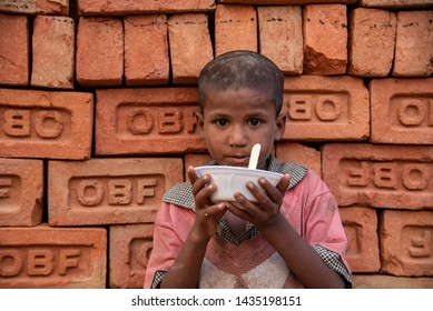 New Delhi, India - June 23, 2019: A young poor boy with his bowl of food in the capital city of India. 20% of the population or 220 million people in India are below poverty line