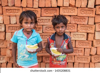 New Delhi, India - June 23, 2019: Two young poor boys with their bowl of food in the capital city of India. 20% of the population or 220 million people in India are below poverty line