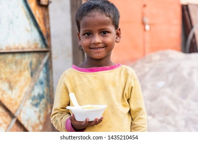 New Delhi, India - June 23, 2019: A poor young kid smiling and holding a bowl of food in his hand.