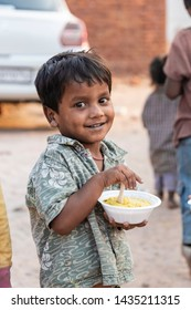 New Delhi, India - June 23, 2019: A poor young boy smiling and holding a bowl of food in his hands in a slum area.