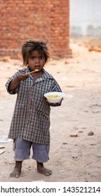 New Delhi, India - June 23, 2019: A poor kid eating from a bowl in a slum area.