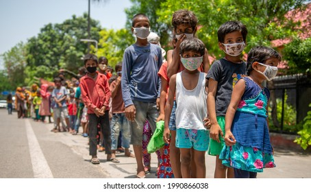 New Delhi, India- June 7 2021: Indian children wearing face masks receive food packets. Food packets are distributed to poor people by religious organization  in New Delhi