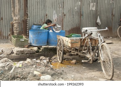 NEW DELHI, INDIA - MARCH 10: Unidentified Indian boy washes dishes on his own tricycle on March 10, 2014 in Delhi, India. Street dishwashers in demand among Indian fast-food restaurants.