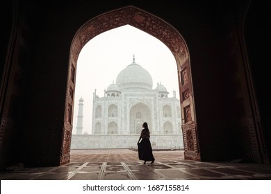 New Delhi / India - March 15, 2020: East Asian young woman (Chinese ethnic) tourist alone in Taj Mahal in the early morning, with no other people