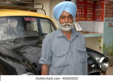 NEW DELHI, INDIA - MARCH 20, 2006: Sikh cab driver with his taxi at a taxi station of the city of New Delhi