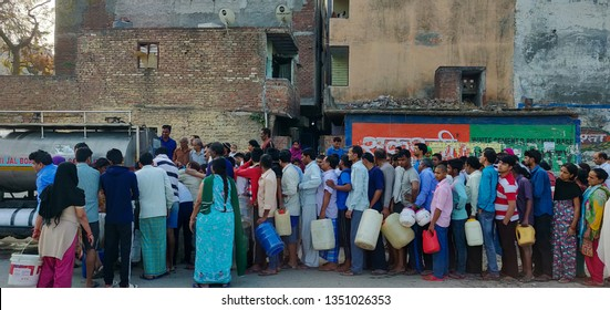 New Delhi, India - March 27 2019: People queue for taking water from Delhi Jal board tanker in the early morning. This shows the water scarcity around the densely populated societies.