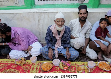 "NEW DELHI, INDIA. MAY 10,2019. : People sit down in great numbers at the Hazrat Nizamuddin Dargah Complex, Delhi to break their fast after sunset - ""Iftar"", during the holy month of Ramadan."