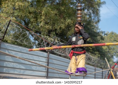 New Delhi, India - May 16 2019: A girl walking on tight rope in city street.