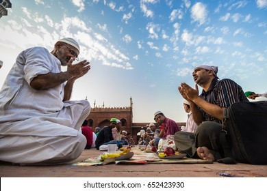 """NEW DELHI, INDIA. MAY 31,2017. : People sit down in the courtyard of Jama Masjid, Delhi for 'Iftar"""" - Meal to break fast after Sunset during the holy month of Ramadan."""