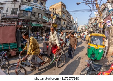 NEW DELHI, INDIA - NOV 17, 2011: man carries  cargo and people with his rickshaw  in old Delhi, Chawri Bazaar.