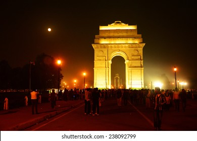NEW DELHI, INDIA, NOVEMBER 07, 2014: India gate against the moonlit sky. Visitors throng at the famous War memorial, a tourist attraction. Misty cityscape lit by streetlights and the full moon.