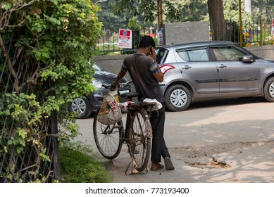 New Delhi, India - November 30, 2017: A man standing near his bicycle and talking on his mobile phone.