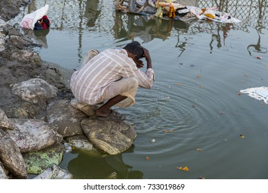 New Delhi, India - October 1, 2017: A man washing his head from the polluted water of river Yamuna.