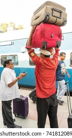 New Delhi, India - October 1, 2017: Unidentified man carrying bags on top of his head at New Delhi Railway station.