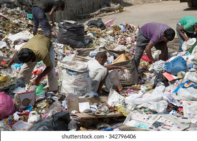 NEW DELHI, INDIA - OCTOBER 11, 2015: Big garbage heap and unidentified people looking for something in the garbage on the street on October 11, 2015, New Delhi, India.