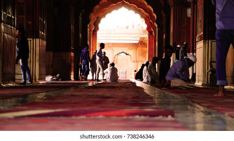 New Delhi, India - October 17, 2017: Jama Masjid in details. New Delhi. The prayer hall in the mosque. Muslims during prayer. Carved arch on the background.