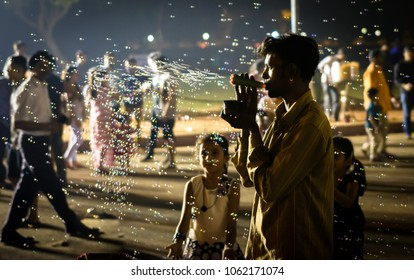 NEW DELHI, INDIA - October 19, 2017: Kids playing with the bubble machine vendor blowing soap bubbles into the air at India Gate in New Delhi, India