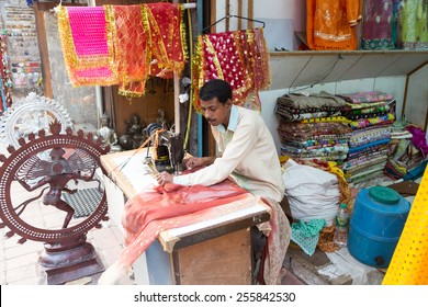 New Delhi, India - October 6 2013: An Indian craftman works on a sari, a traditional cloth for women, in front of the shop in the streets of New Delhi, India capital city.
