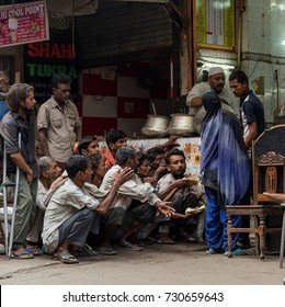 New Delhi - India, October 7, 2017: Poor hungry people waiting outside a restaurant for free distribution of food in old Delhi.
