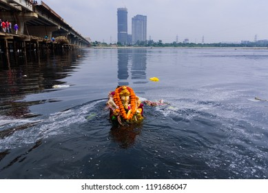 New Delhi, India - September 23, 2018 : A devotee immersing the idol of Hindu god Ganesha in polluted waters of river Yamuna in New Delhi, on last day of  festival Ganesh Chaturthi festival.