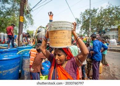 New Delhi, India-June 25 2021: woman carrying drinking water bucket on head, shortage of Drinking water in delhi during summer, government or municipal corporation supply water by tankers