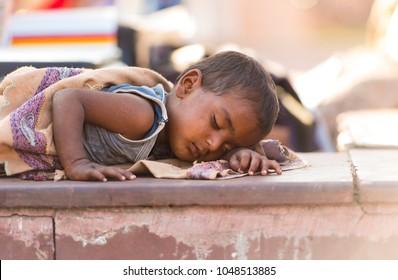 NEW DELHI - MAR 02: sleeping poor boy in a street in New Delhi on March 02. 2018 in India