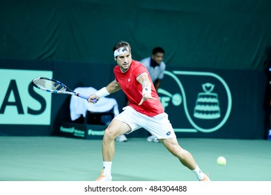 NEW DELHI - SEPTEMBER 16, 2016: David Ferrer of Spain plays against Saketh Myneni of India in the second singles match of Davis Cup World Group Play Off tie at R.K. Khanna Tennis Stadium, New Delhi.