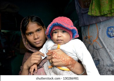 NEW DELHI,INDIA-FEBRUARY,4: a young Indian mother with her child who lives in the poorest district of New Delhi in February 4,2013.50% of the population of New Delhi is thought to live in slums
