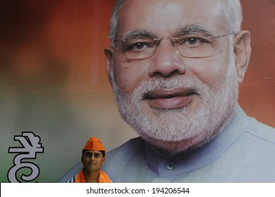 NEW DELHI-MAY 16:   A BJP supporter  standing in front of a Narendra Modi image at the party headquarter after BJP  won the Indian National election on May 16, 2014 in New Delhi , India.