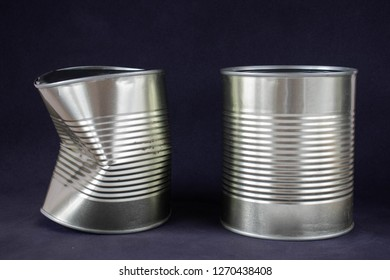 A new and a dented can on a black background