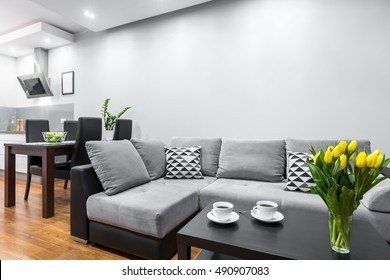 New design home interior with big sofa, wooden dining set and open kitchen