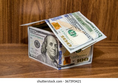 new dollar house, money building, isolated on wooden background