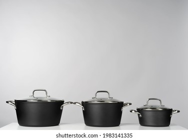 New domestic cookware on grey background close up