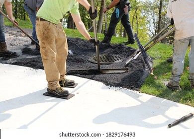 A new driveway is being installed, with hand finishing work needed around a storm drain and gutter.