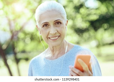 New earphones. Positive smiling senior woman listening to music in her new white earphones