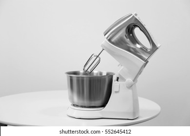 New electric mixer on table against light background