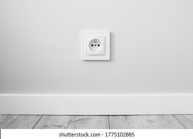 New electrical socket isolated on gray wall. Renovated studio apartment power supply background. Gray wooden floor. Empty copy space white plastic power outlet.